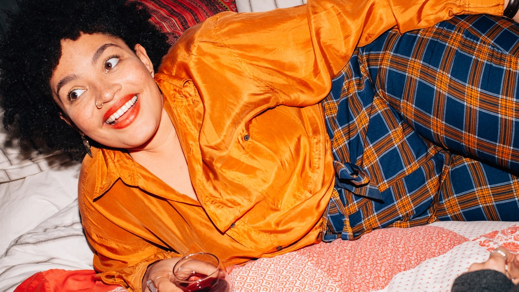 A young Black woman lays in bed with a glass of red wine on her birthday and smiles in a brightly-colored outfit.