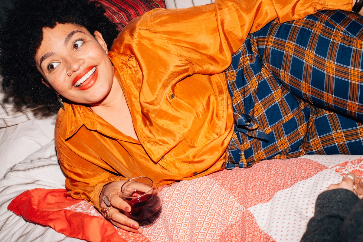 A young Black woman lays in bed with a glass of red wine on her birthday and smiles in a brightly-co...