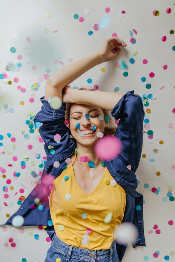 A young woman dances in confetti while somebody takes her picture on her birthday.