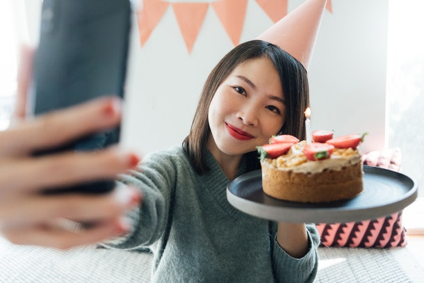 A young Asian woman poses with her birthday cake and takes a selfie on her phone.