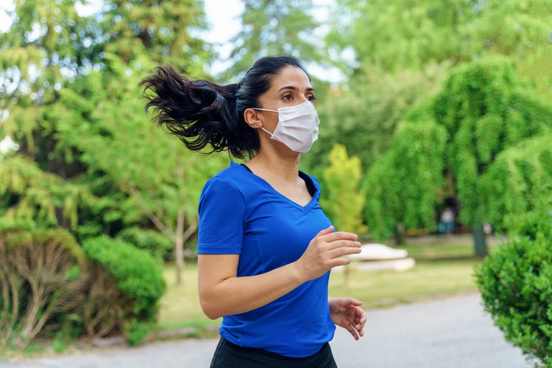 A person in a lblue v-neck wears a mask while running in a park. If you've started working out during quarantine, keeping those habits as businesses reopen can be difficult.