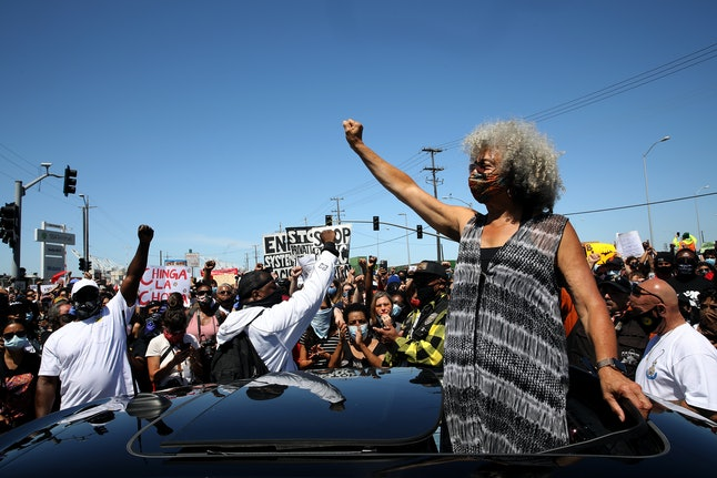 A woman stands above her car at a Black Lives Matter protest. Social distancing is hard at protests, but coronavirus cases have not risen as a result of protesting.