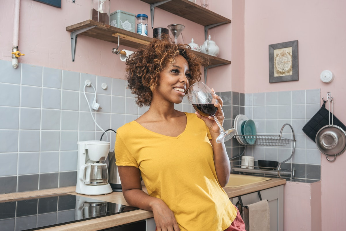 A relaxed woman sips a glass of red wine in her kitchen.