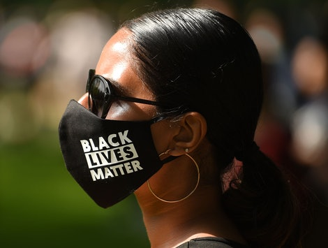 A woman wears a face mask saying Black Lives Matter at a protest. A paper reports that protests didn't increase coronavirus cases.