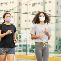 Two people run together outside while wearing masks. Even when your gym is closed, it is indeed possible to exercise too much.