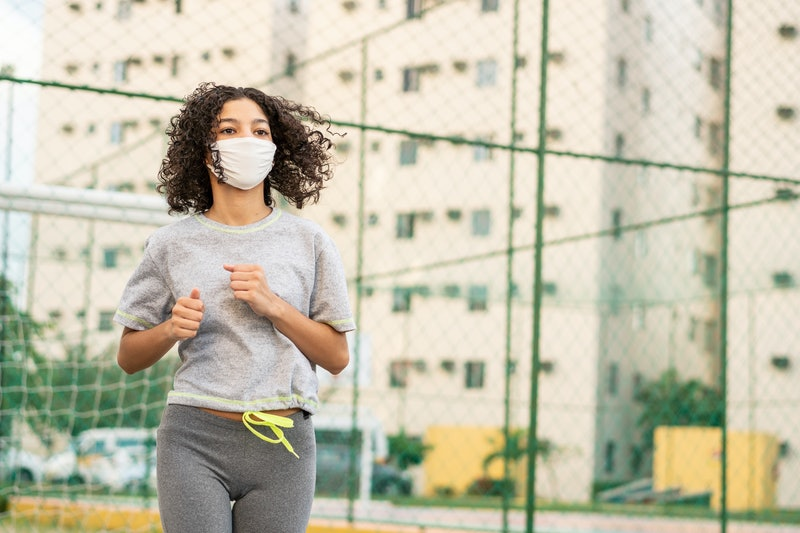 A person wearing a grey short-sleeved running tee goes for a jog outside while wearing a mask. You might have taken quarantine as a sign to get your running on.