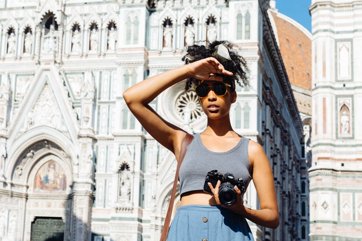 A young Black woman stands in front of the Duomo in Florence, Italy with her camera on a sunny afternoon.