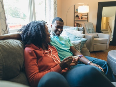 pregnant woman and man sitting on couch with pregnancy test