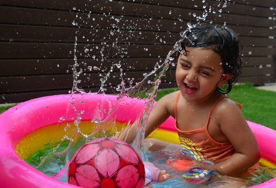 little girl playing in inflatable pool in backyard