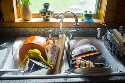A sink full of dirty dishes. If You Find Yourself Snapping At Your Roommate In Quarantine, Here's expert tips To Do A Little Better
