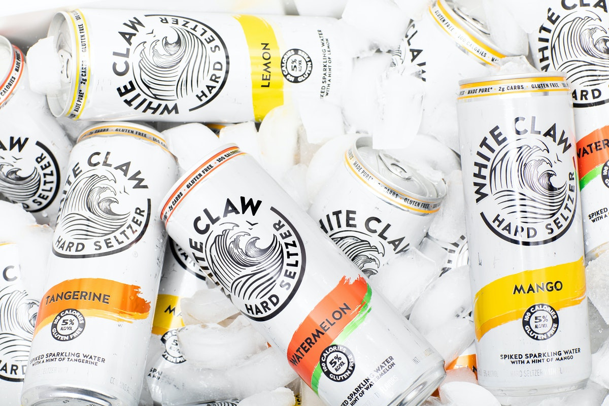 White Claw cans sit in a cooler with ice cubes.