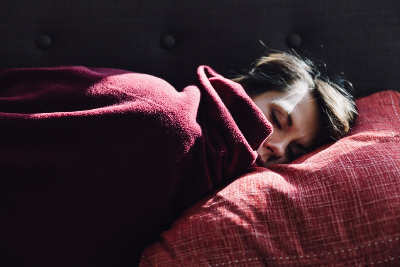A woman sleeps under a red blanket. Experts Explain How Apple's New Sleep Tracking Feature Can Affec...