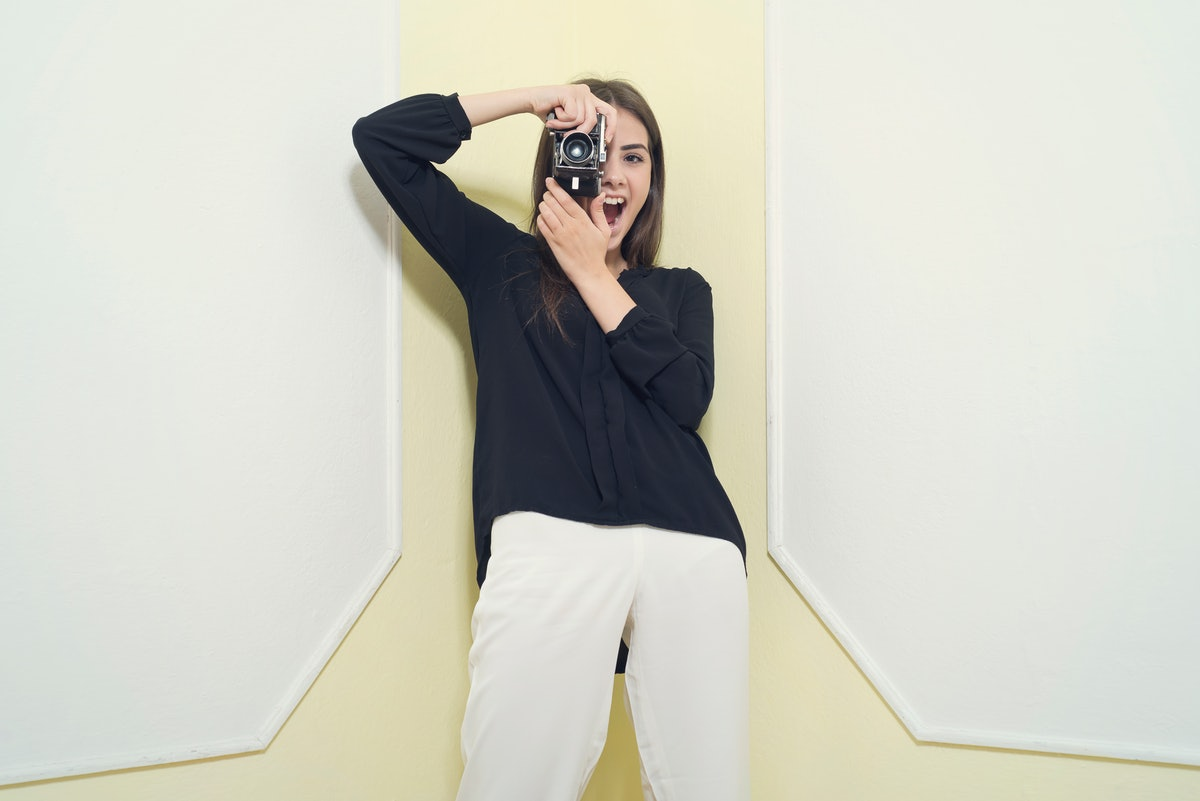 A young woman poses in front of a white and yellow backdrop with her digital camera.
