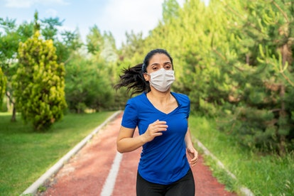 A person wearing a blue tee and a mask runs on an outdoor track. Especially when you're stressed out, the risk of working out too much during the pandemic is extremely high.