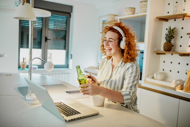 A young woman laughs while holding up a beer and video chatting in her apartment.