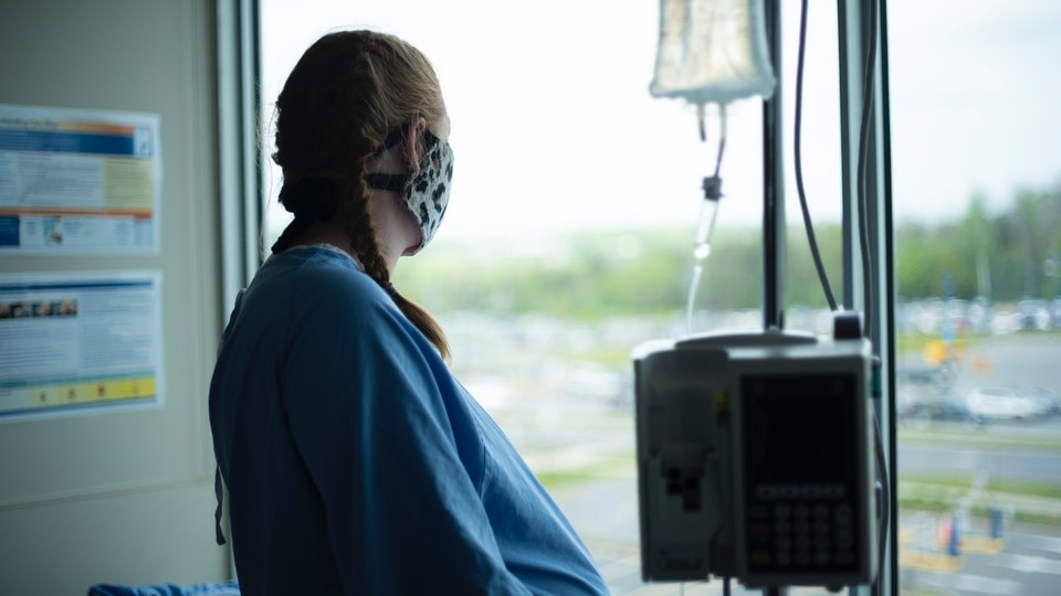 pregnant woman looking out window at hospital wearing mask