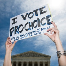 """A woman holds a sign saying """"I vote pro-choice."""" Tennessee's 6-Week Abortion Ban Hurts Patients & Providers, A Doctor Says"""