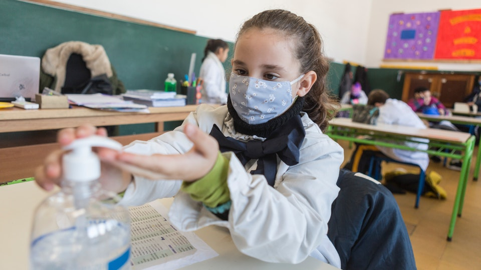 girl in face mask sanitizes her hands at school