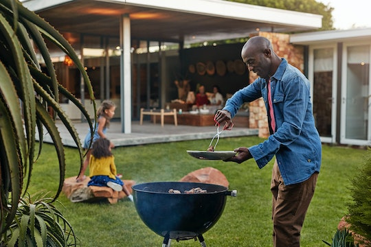 a black dad grilling in the backyard with kids sitting on lawn
