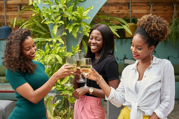 Three young Black women clink their glasses of white wine while hanging out in their backyard.