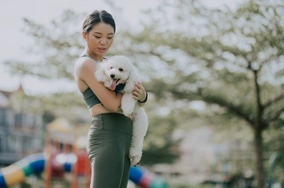 A person wearing dark green workout clothes holds their white puppy close to their chest in a park. Carrying your dog around outside can be a lovely way to bond while working out.