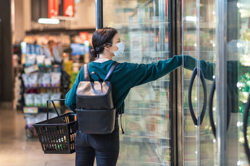 A woman wears a face mask at the grocery store. 8 Myths About Wearing Face Masks To Protect Against Coronavirus, Busted By Doctors