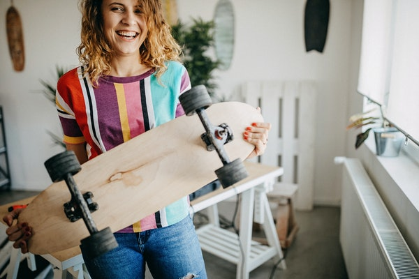 A young woman laughs while holding a skateboard in her home.