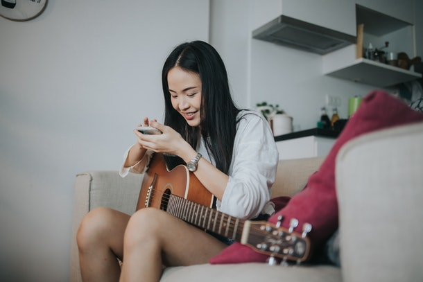A young Asian woman holds a guitar on her lap while playing with her phone.