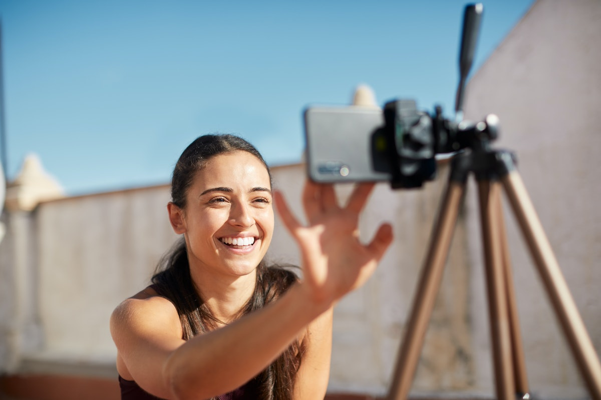 A young woman smiles while setting up her video camera outdoors on a tripod.