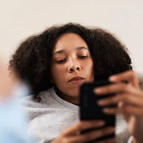 A woman looks at a text message debating whether to answer it. Experts explain why answering texts feels so exhausting right now.