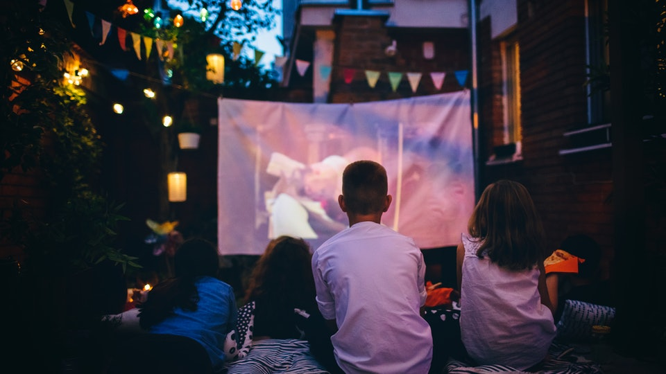 family having backyard movie night