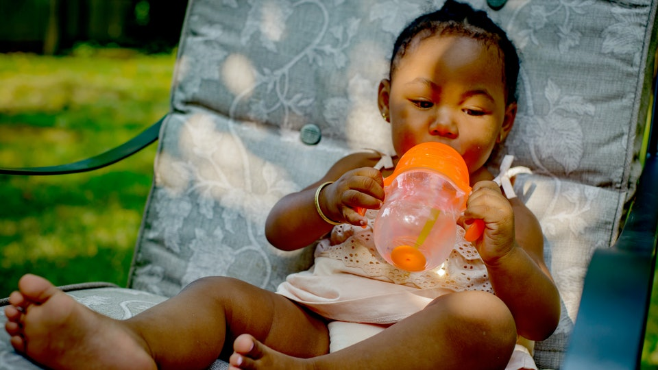 black baby girl sitting on chair outside with sippy cup