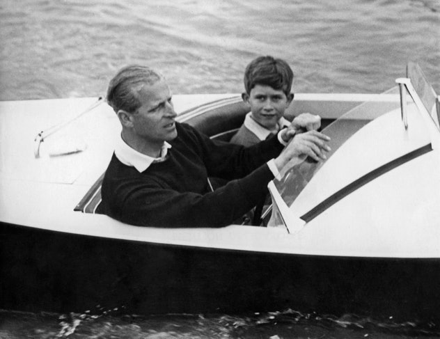 Prince Philip drives his son Prince Charles in a boat.
