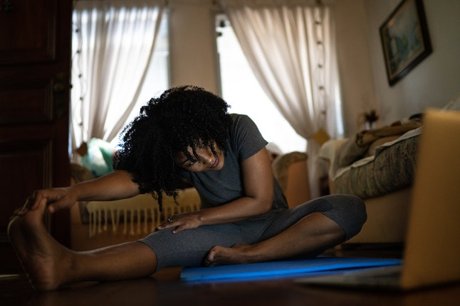 A person with natural hair wearing yoga pants sinks into a stretch on their yoga mat at home while taking guidance from their laptop. Working with an online personal trainer can be a great way to get active during quarantine.