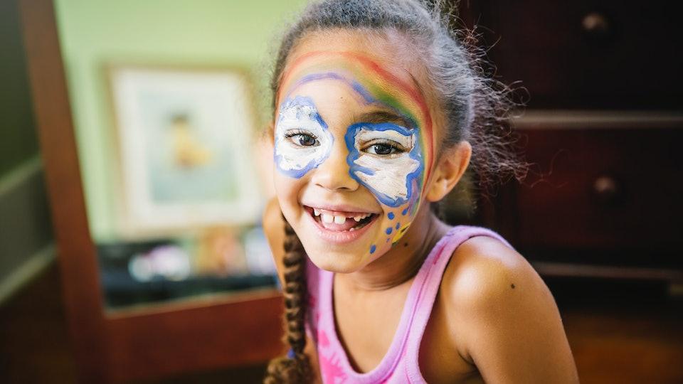 little girl with rainbow face paint