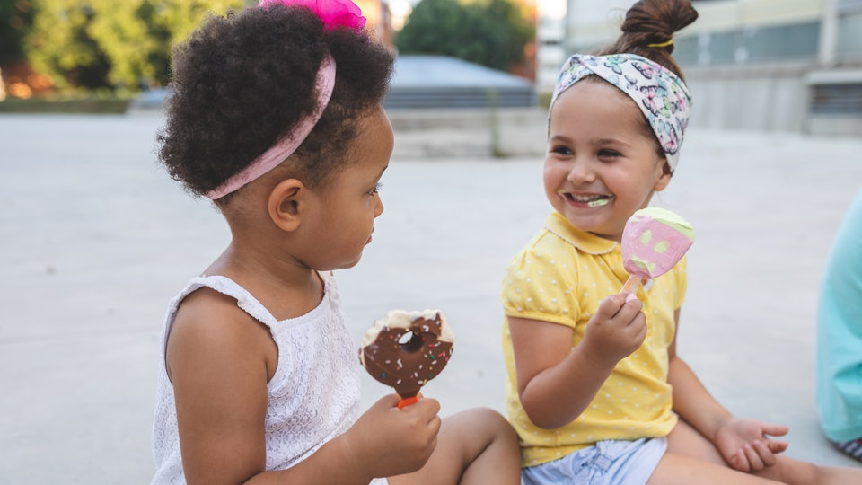 black and white toddler girls eating ice cream at park