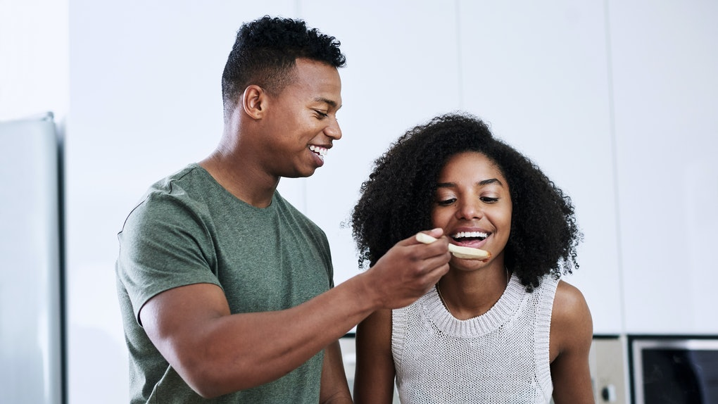 A young Black couple tastes what they're making in the kitchen with a wooden spoon.
