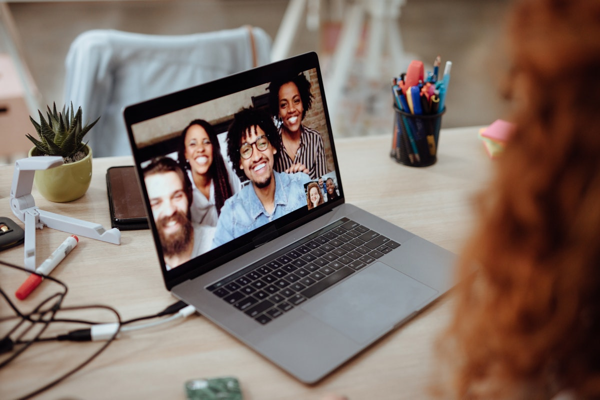 A family smiles into a video chat on their laptop, and poses for a picture.