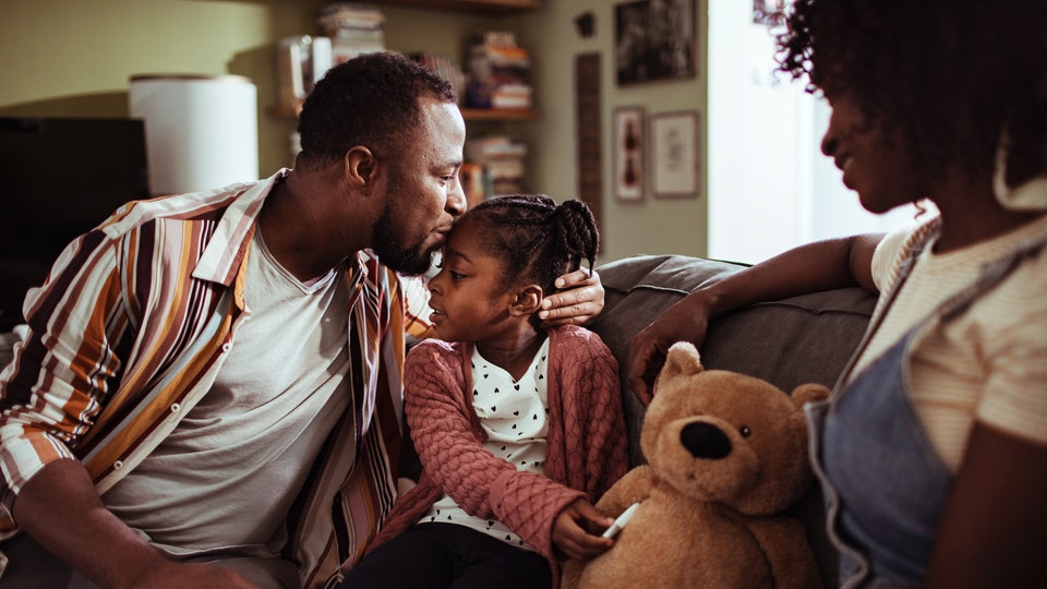 a Black mom and dad on couch with daughter and teddy bear