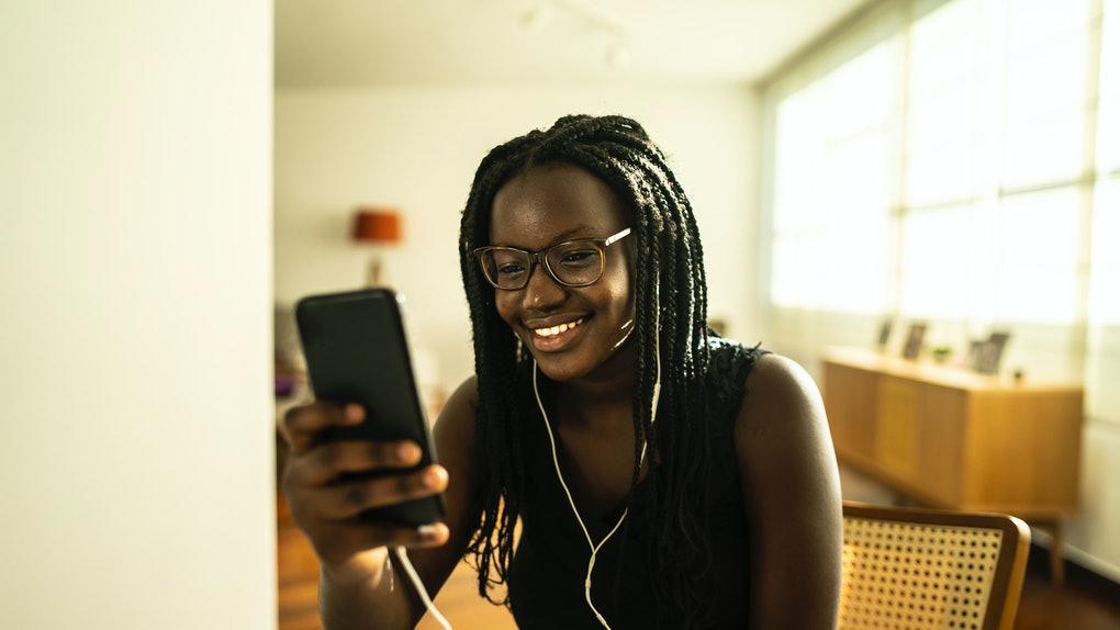 A young woman sits at her kitchen table and video chats on her phone while wearing headphones.
