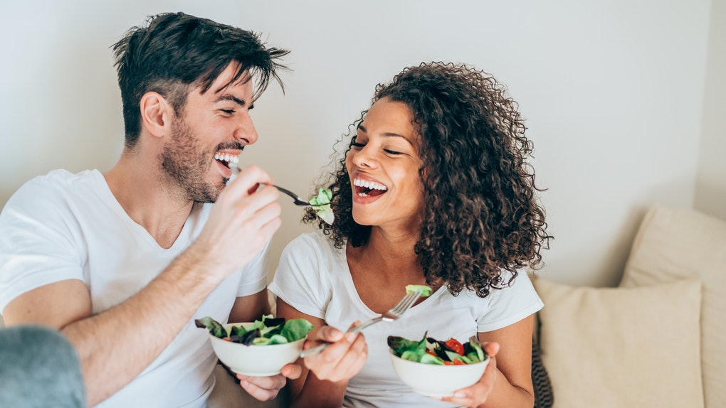 A young couple laughs and eats salads while sitting on their couch on a lunch break.