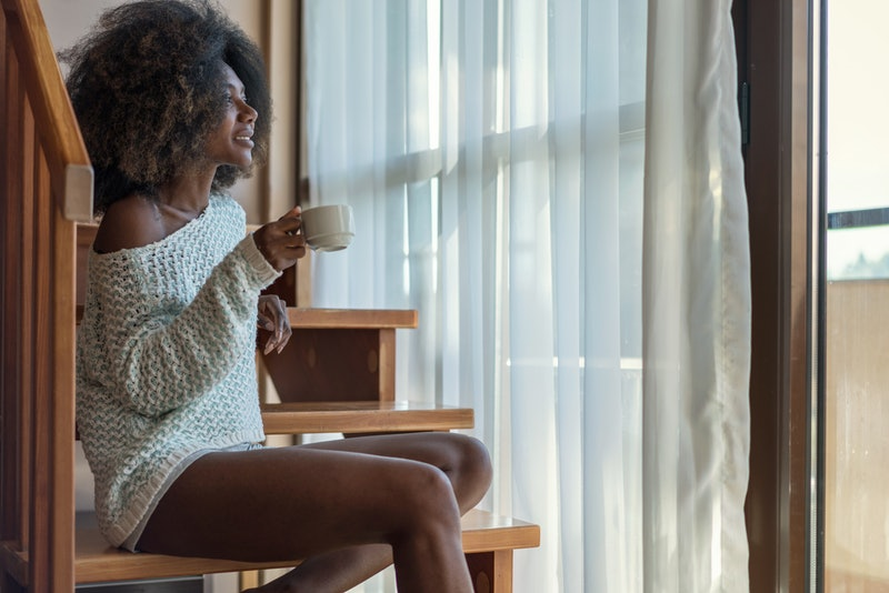 A person wearing an off-the-shoulder sweater sips coffee while looking outside their window. Self-care isn't just about a single relaxing evening.