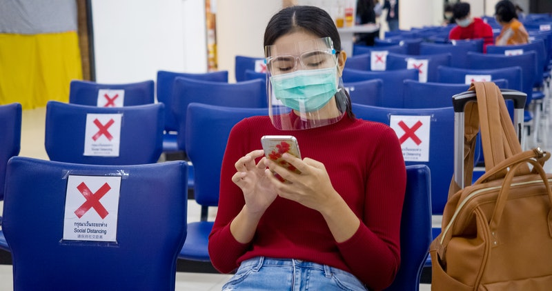 A woman puts on a face shield over her face mask in an airport. Plastic face shields are gaining popularity as a potential way to prevent the spread of coronavirus.