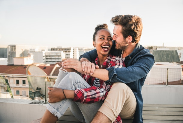 A young couple laughs while sitting on their rooftop and waiting for a sunset.