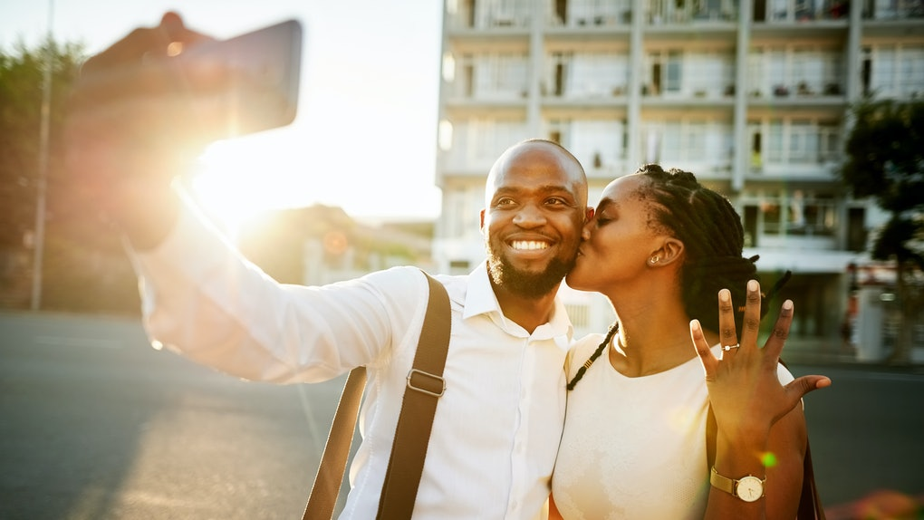 A young couple takes a picture during golden hour after getting engaged.