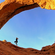 A woman runs inside a desert rock formation. Experts weigh in on ways to run better in the heat.