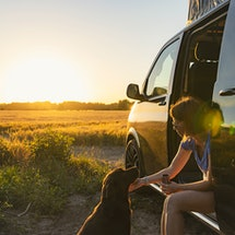 A woman with a dog in an RV. Traveling and taking vacations during the COVID-19 pandemic requires precautions.