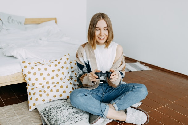 A young woman smiles while playing video games in her room.