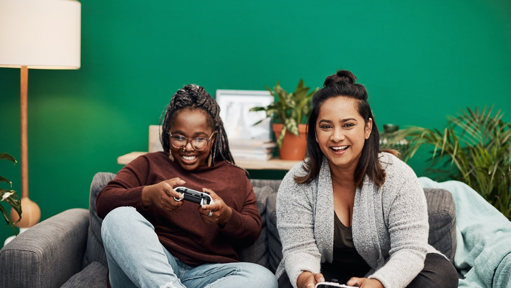 Two young women sit on a couch in front of a bright green wall and play video games.