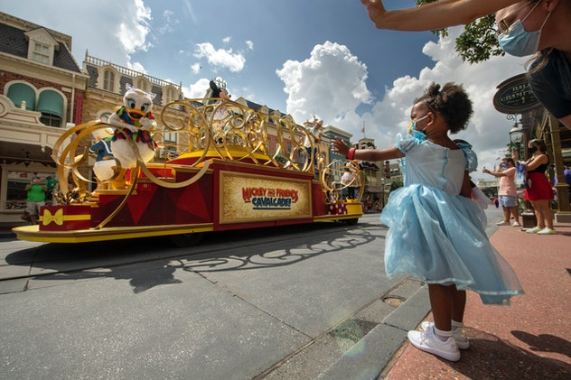A little girl waves at the Disney cavalcade.